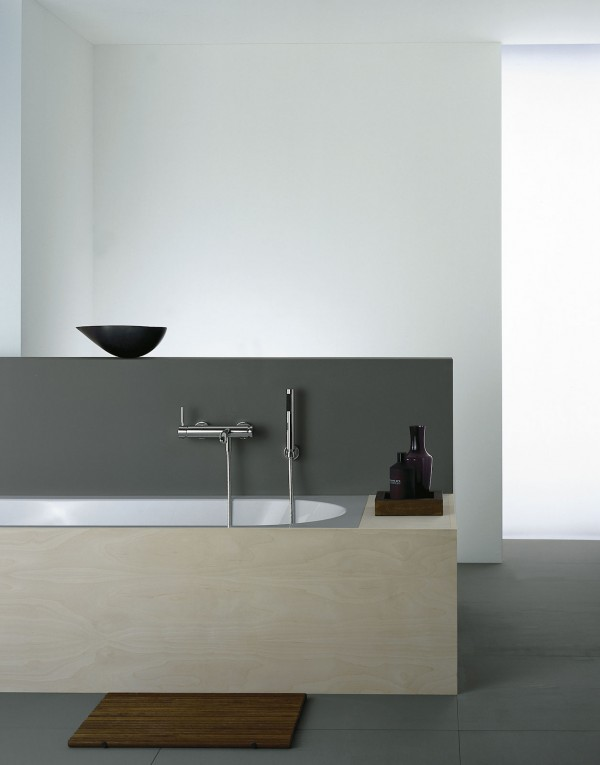 A simple soaking tub boasts blocks of texture and tone in the wood tub surround and a gray dividing wall. A single black bowl set atop the wall adds drama.