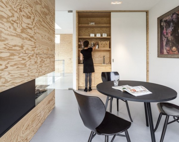 Sliding doors hide a small kitchenette with sink and pantry. A black dining table and chairs contrast nicely with the raw wood of the fireplace surround.