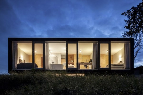This nighttime exterior view shows the villa's upper level of bedrooms and bathroom.