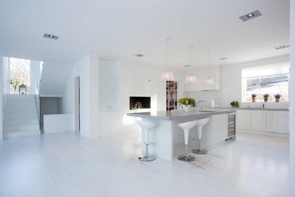 The brilliant white kitchen has a nice size island with bar seating as an eat-in feature. Painted white wood floors bounce the light throughout the space.