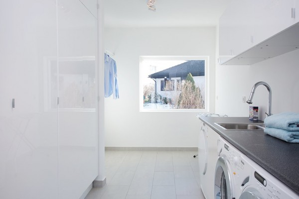 A nice size laundry room features plenty of built-in behind door storage and built-in washer and dryer within the cabinetry.