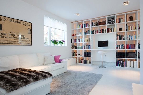 The family room with built-in library and work station allows for many leisurely and work-related pursuits. The book shelves boast a lovely backlit feature that highlight the colorful book collection.