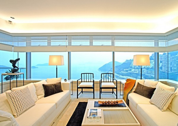 The view of the coast and sea beyond is well framed with a surround of large windows in this warm and welcoming modern living space. A grouping of chairs and sofas offers an inviting conversation area.