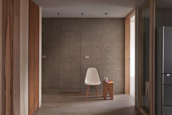This passageway is the perfect example of dramatic minimalism. A single chair and small wood table set against a rough, unfinished concrete wall.