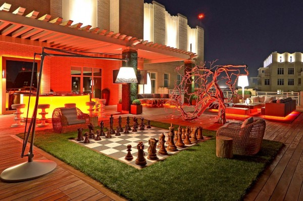 A city rooftop plays host to a dramatically-lit yet fun outdoor living space with life-size chess board.