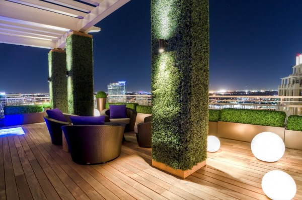 Living columns covered in dense greenery give this modern outdoor space a natural touch. Randomly placed light globes provide an air of mystery.