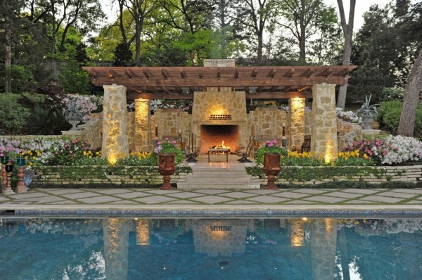 Pools and water features have long been a central element in outdoor living spaces. This one offers a cool element contrasting with the warmth of the fire and lighting in the living area beyond.
