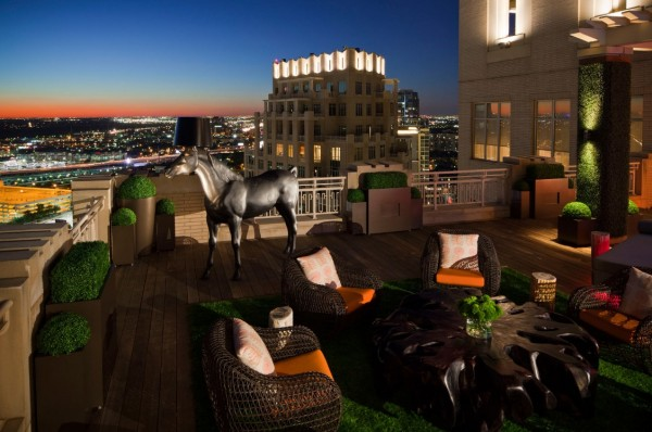 The city skyline sits in the backdrop of this comfort-minded terrace furnished with contemporary seating and organic elements.