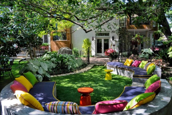 Vivid color is the order of the day in this unusual garden space with curving bench-like seating filled with brightly-hued textiles and plentiful toss pillows.