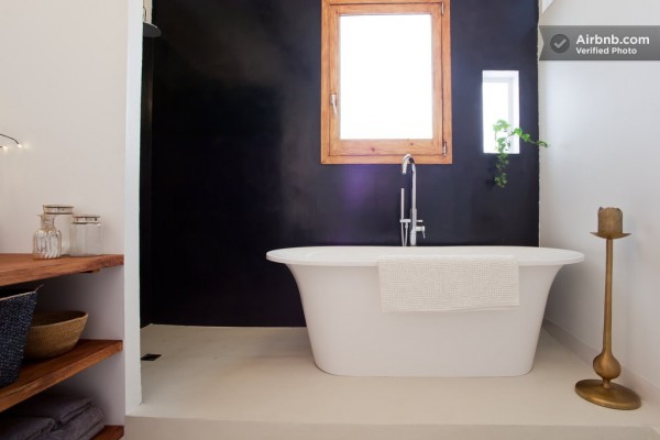 A large soaking tub takes center stage in front of a dramatic black wall.