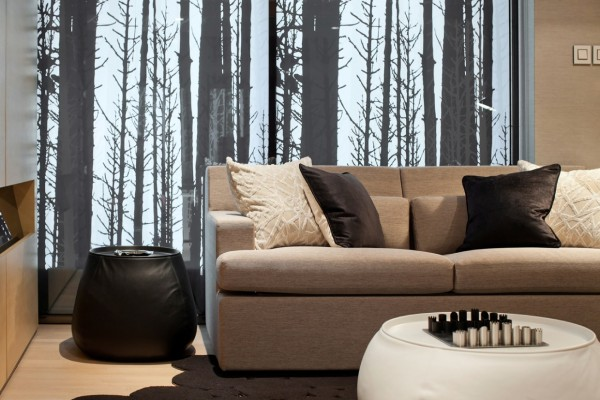 A large mural depicting a barren winter forest sets the mood in this contemporary living room. Warmth comes into play with warm wool upholstered sofa, velvet pillows in chocolate brown and grasscloth wall covering.