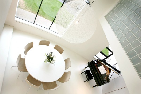 An enormous string globe light fixture echoes the large round table below while a baby grand piano sits tucked into a corner of the open space living area.