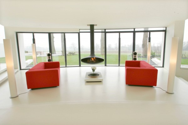 Twin vivid red sofas arranged symmetrically in between four identical floor lamps with suspended fireplace in the center.