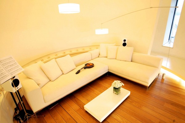 A music room sits in one of the circular rooms of the tower itself. A cream-colored modern sectional provides ample seating in the tiny space.