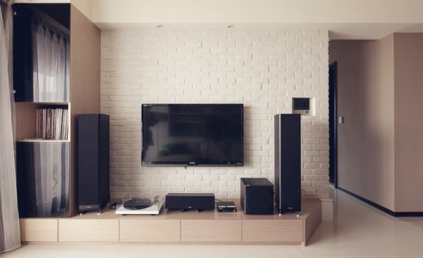 A low profile wood platform with drawer space acts as media center set in front of a painted brick wall.
