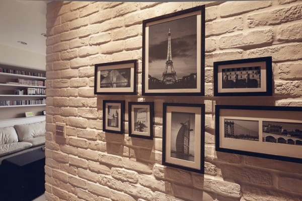 A gallery art wall featuring small black and white photographs is dramatically lit from above.