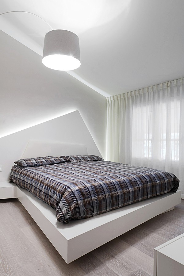 The uber-modern bed is in direct contrast to the traditional plaid bed coverings.