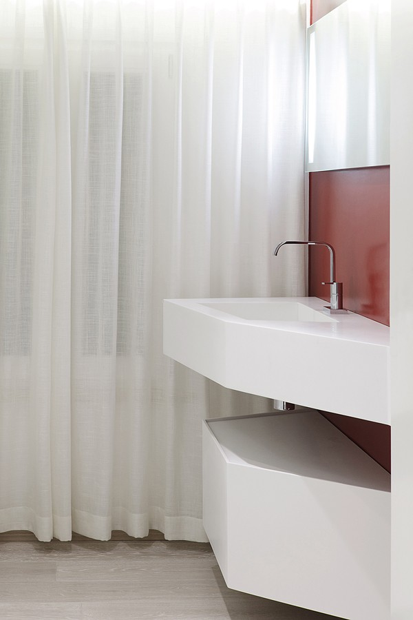 True to elements throughout the house, the bathroom vanity is cut-out and angled in a striking use of line.