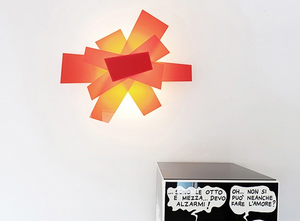 A backlit modern art sculpture of acrylic adds a touch of color to the otherwise black and white space.
