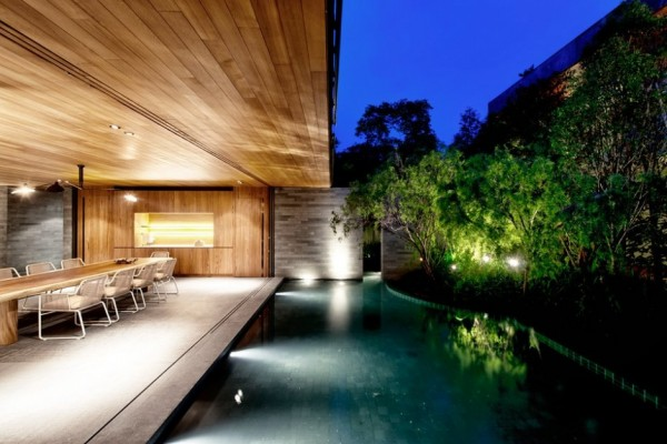 The shallow pool adds a mysterious element to the outer living areas as it winds around the house.