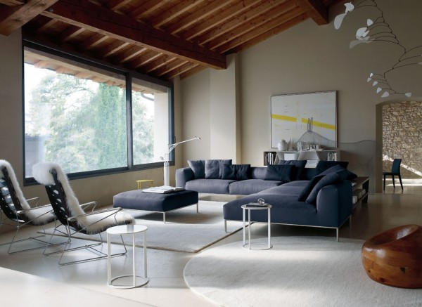 Using different shapes is key in this design. The square and rectangular sofa mixed with round accent tables adds diversity to the space. The fur chair covers warm it up.