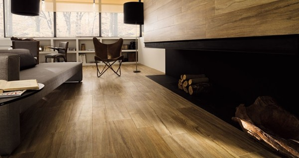 The elongated, built-in fireplace is surrounded by natural wood panels that also cover the floor.