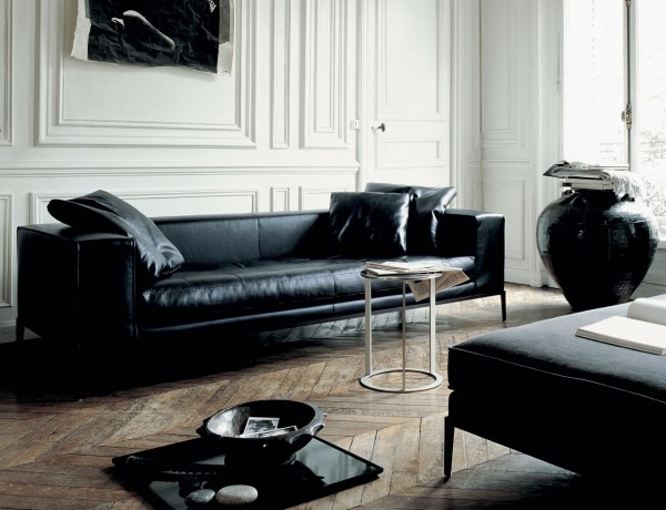 This room has classic charm and traditional design elements with the rustic hardwood floors and decorative moldings but is brought up to date with the addition of this modern black sofa and black accent furnishings.