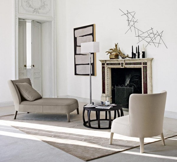 A cozy spot in front of the fire place is created here with a neutral chaise lounge and an armchair. The black in the table and accent pieces add a bit of contrast.