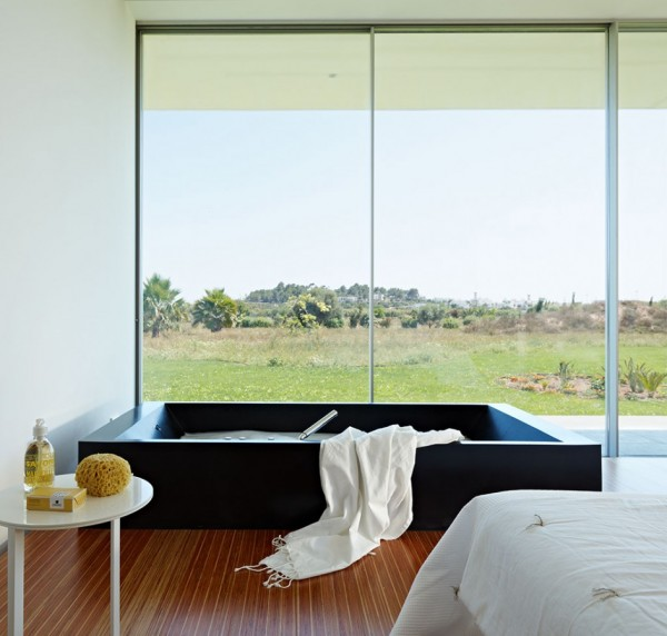 Even the bathroom of this minimalist home puts design on the forefront. This simple, sunken bathroom looks out over the surrounding landscape. To bathe while looking to the outdoors is the ultimate in luxury while the smooth, unadorned design is