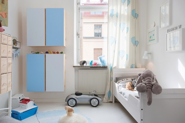 For a growing family who is not afraid of some stains, the children's room is also replete with whites and blues, including practical built-in cabinetry for storage and gauzy, adorable curtains decorated with baby blue balloons.