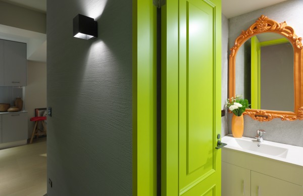 The overall palette of the house is cool neutrals, but shocks of neon in the guest bathroom send a clear message that this modern design does not take itself too seriously. This mirror is a perfect example. Its traditional and elaborate shape finds a place in this apartment only when covered with a vibrant orange lacquer.