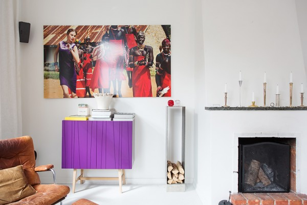 Although most of the walls in the apartment are a shockingly clean white, the designer brings in many colorful elements that pop in the sun. This bright violet cabinet cannot be ignored, even as it is flanked by a deliciously worn leather chair/ottoman combination and a built-in fireplace.