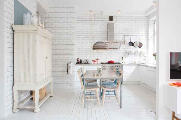 The kitchen and dining area bring the white theme to new heights with white tiled walls and greyish white marble countertops. A funky silvery light fixture is an interesting design focal point, even when its bulbs are unnecessary.