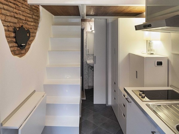 With the table tucked away, a narrow staircase leads up to the bedroom and living area, where a trapdoor can be closed behind you so you don't accidentally slip back downstairs.