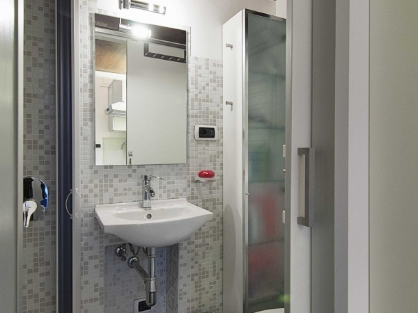 The bathroom is small but gleaming with just enough space for comfortable showering and daily rituals.