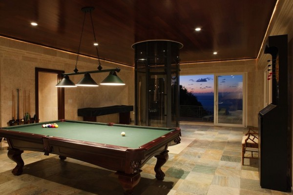 Located on the pool level of this three-level mansion is a game room, including billiards table along with a fully equipped wet bar and two guest suites.