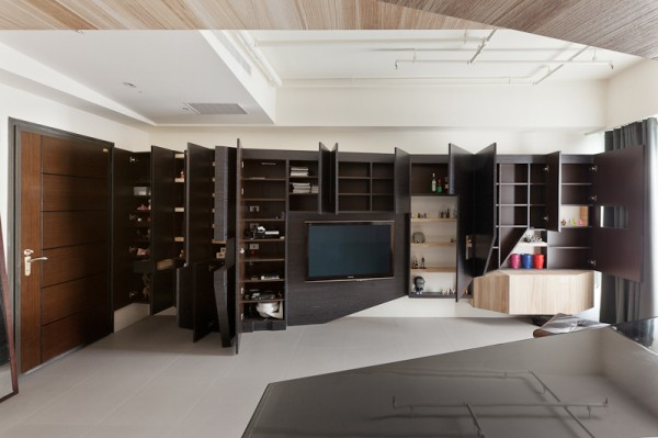 The massive built-in storage unit in the living room creates a black accent wall when closed, and tons of hidden storage space when every door opens up.