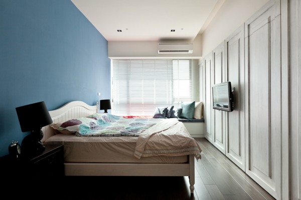 The narrow bedroom with a subtly blue wall behind the bed is a little more playful than the other rooms, including a cozy window seat and interesting paneled wall.
