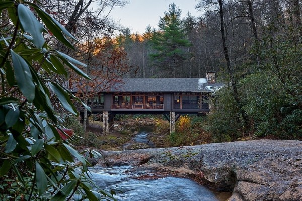 The cabin itself actually spans a river, balancing atop heavy stone columns and giving unparalleled views of the surrounding forest.