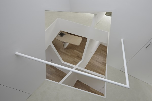 "From a different angle, we can see how the ""holes"" in the floor offer a view all the way up and down, giving a clear impression of the cube theme that pervades the house."