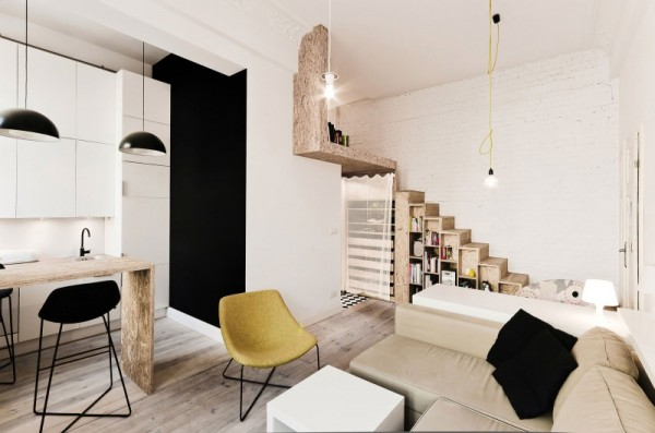 The entire apartment is visible in this single photograph. From storage space under the stairs to a nested dining table/desk, every square inch is carefully considered and put to its best use.