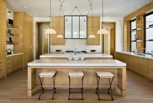 In the kitchen, work areas are marked out by low hanging pendant lights to provide task lighting over marble benches. Again, the color scheme is kept calm, this time with blonde wood cabinets and cream bar stools.