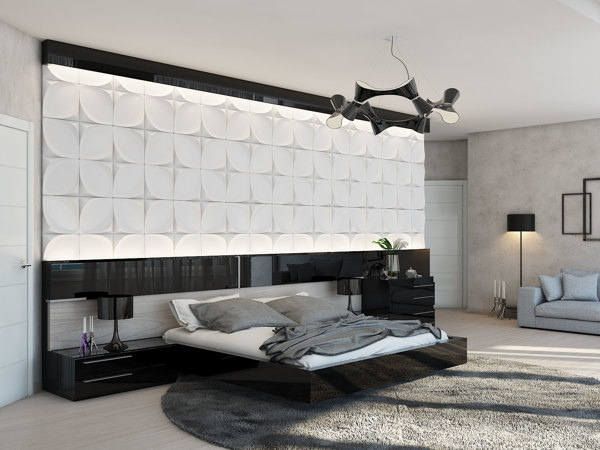 This bedroom setup boasts a huge headboard feature wall, where concave tiles play with light and shade. The black gloss bed base flows seamlessly into the bedside cabinet, and is echoed by panels above the bedstead.