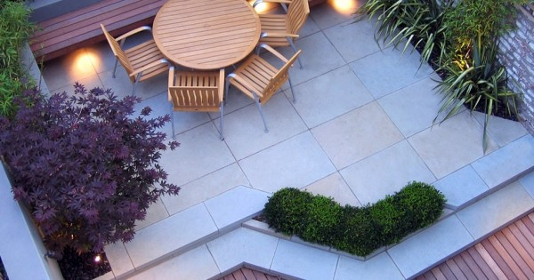 Planters can also be built right into the patio to blur the edges between zones. Note the beautiful selection of different colored leaves; not all color in a garden needs to come from flowers. In this design the built-in bench has been utilized as extra seating at the table–great for unexpected guests!