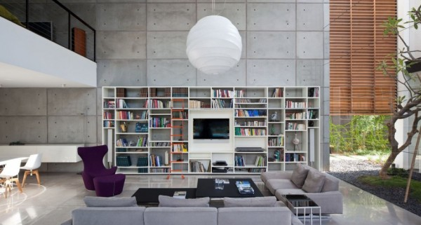 The modern library space almost echoes out of the photos with its cement accent wall and suspended lantern that acts as the sun and the moon.