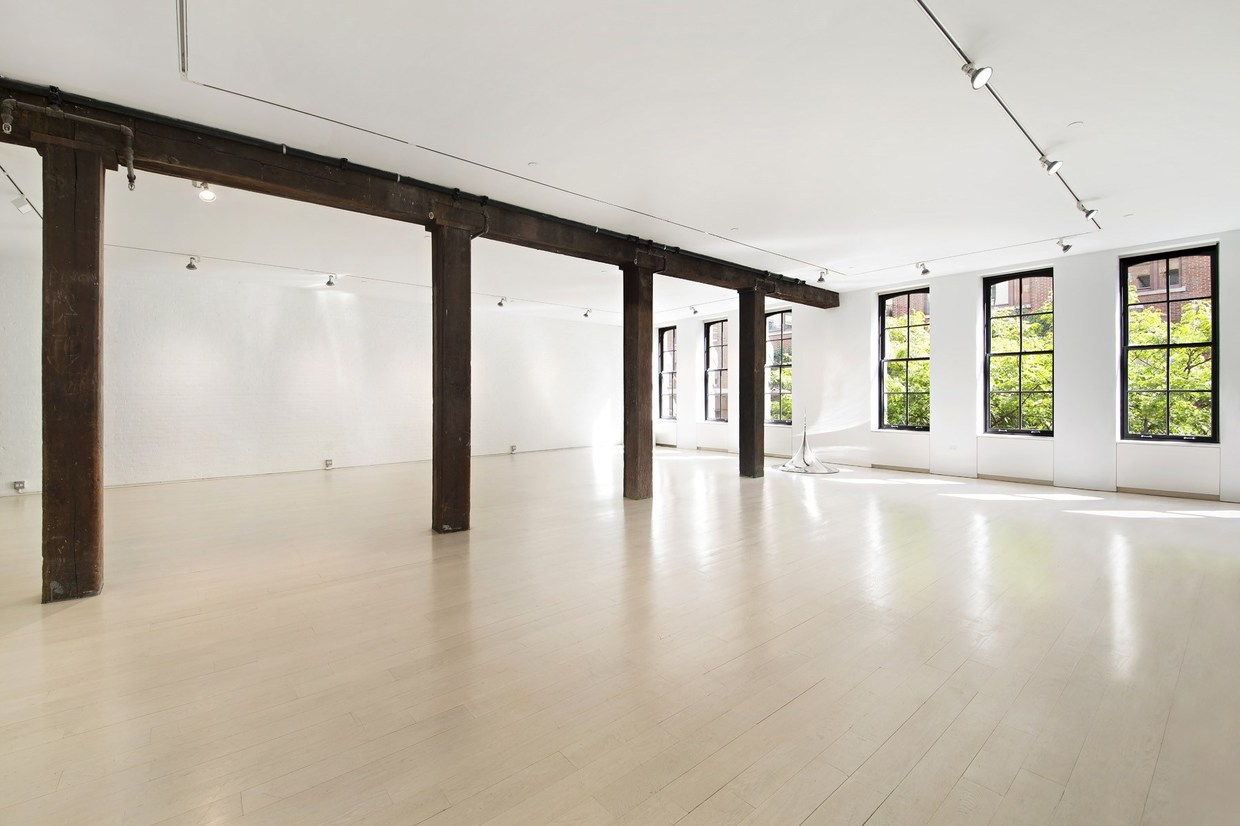 The lowest floor is an open space with dramatic exposed beams. It's ready to become a gallery or creative space but it has the bones to become anything: office, gym, bedrooms, etc.