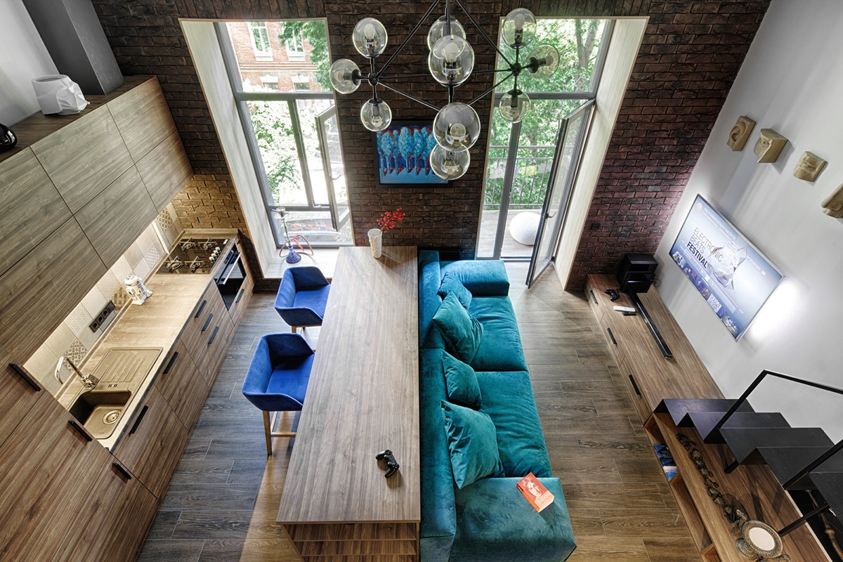 A 49-metres-squared loft in Kiev by Ivan Yunakov (http://yunakovdesign.com) also uses signature shades to create harmony in cosy spaces. High-ceilinged brick and panelled wood fixtures afford the height for long-lined doors, which are stretched horizontally by similar-shaped benches. A turquoise couch with electric blue suede single seats offer seats to look at bauble lighting, the only rounded fixture in the room.